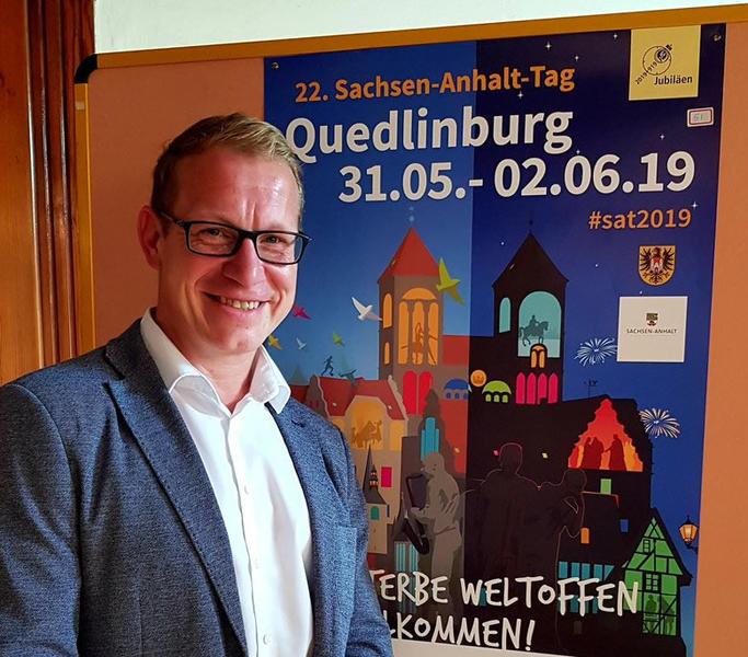 Das Bild zeigt Norman Groß vor dem Siegerplakat zum Sachsen-Anhalt-Tag 2019 in Quedlinburg.